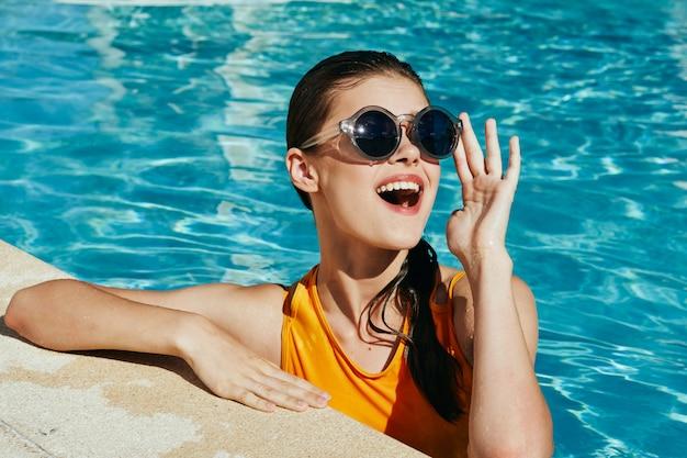 Modefrauenporträt im gelben badeanzug am pool
