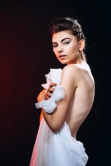 Modefrauenstellung eingewickelt in einem besless stoff, nackte rückseite zeigend