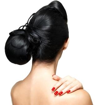 Modefrisur der frau mit den roten nägeln lokalisiert auf weißer wand