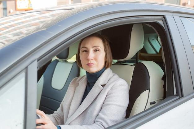 Modegeschäftsfrau im mantel, der auto fährt.