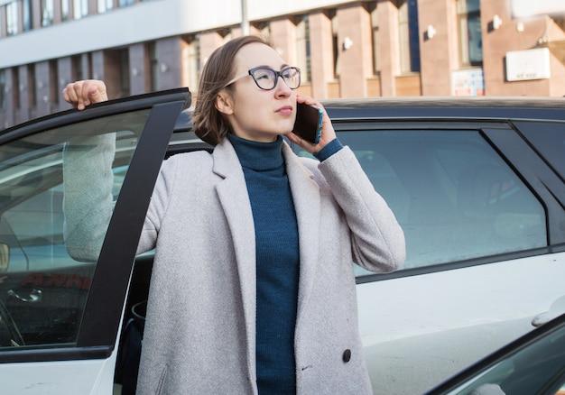 Modegeschäftsfrau in den gläsern mit telefon steigen aus dem auto aus.