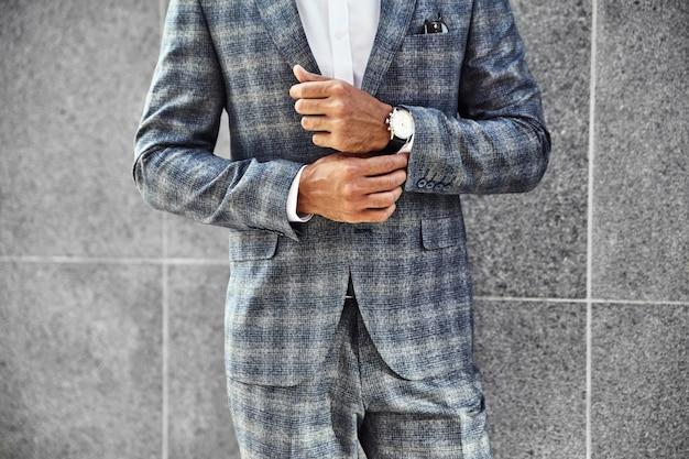 Modegeschäftsmannmodell gekleidet in elegantem kariertem anzug, der nahe grauer wand auf straßenhintergrund aufwirft. metrosexuell mit luxusuhr am handgelenk