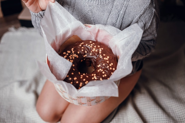 Modeinnenfoto der schönen jungen frau mit roten haaren und charmantem lächeln, trägt kuschelige gestrickte strickjacke, posiert neben weihnachtsbaum und präsentiert mit schokoladenkuchen mit sternchen