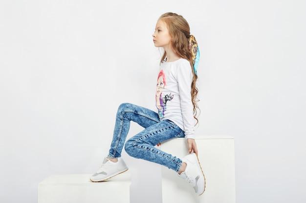 Modekinder posieren für frühlings-denim-kleidung. freude und spaß. jeans
