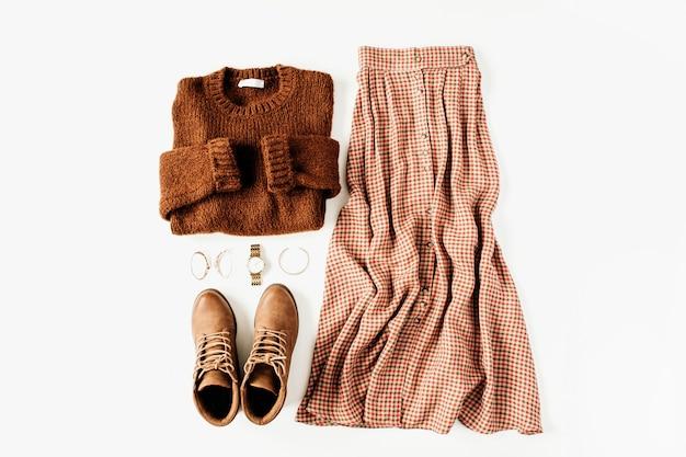 Modekleidung sieht komposition mit braunem pullover, schuhen, rock auf weiß aus