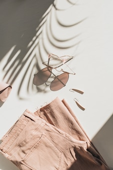 Modekomposition mit damenbekleidung und accessoires auf weiß. ohrringe, sonnenbrille, rosa jean culottes auf weiß