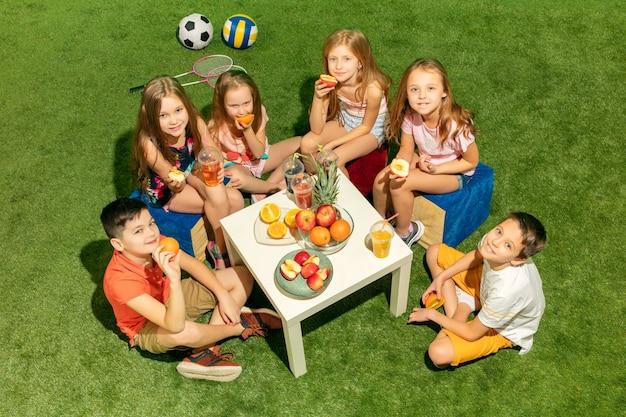 Modekonzept für kinder. die gruppe von jugendlichen jungen und mädchen, die auf grünem gras im park sitzen. bunte kinderkleidung, lifestyle, trendige farbkonzepte.