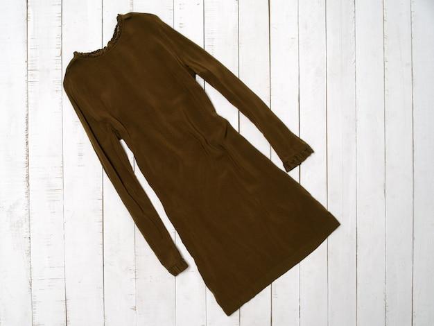 Modekonzept für kleidung. khakifarbenes kleid mit ärmel auf weißer holzoberfläche. ansicht von oben
