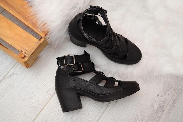 Modekonzept, schwarze weibliche schuhe mit schnallen auf der holzkiste