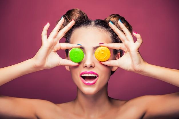 Model, eine frau mit hellem make-up und bunten keksen im scherz. studio, schönheit, glitzer, süßigkeiten.