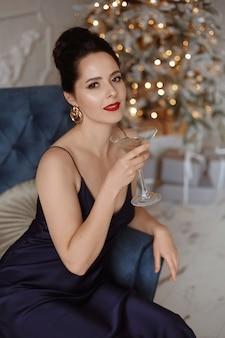 Model frau mit einem glas champagner auf der neujahrsparty champagner trinken über den feiertag festlich...