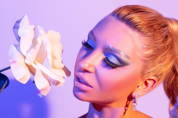 Model-frau mit einem hellen make-up in buntem hellem licht posiert im studio.
