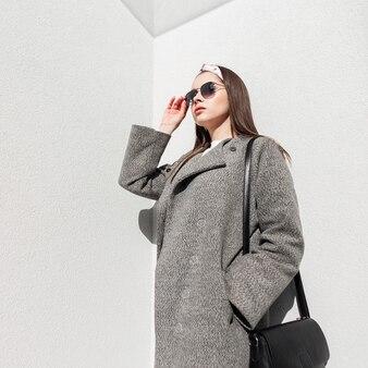 Model-glamour-frau in grauem, elegantem mantel in glamourösem bandana in stilvoller sonnenbrille entspannt sich auf der sonne in der nähe der weißen vintage-wand auf der straße. schönes mädchen in lässiger oberbekleidung genießt das frühlingssonnenlicht im freien