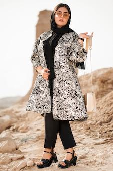 Model im langen kleid mit blumenmustern und schwarzer kopfbedeckung