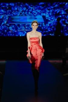 Model im roten kleid auf dem laufsteg