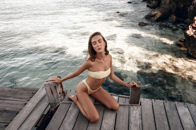 Model in einem engen bikini posiert und sitzt auf einer holzbrücke, die augen geschlossen
