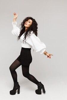 Model-mädchen mit langen schwarzen locken und perfekt schlankem körper trägt eine weiße bluse und schwarze shorts ...