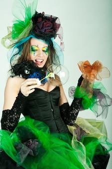 Model mit kreativem make-up, das seifenblasen bläst. puppenstil.