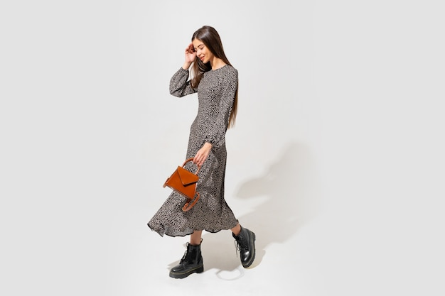 Model mit schönem gesicht und perfektem körper. trägt ein trendiges kleid und hält eine braune lederhandtasche. volle länge.