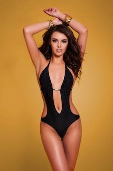 Model posiert in einem badeanzug auf goldwand