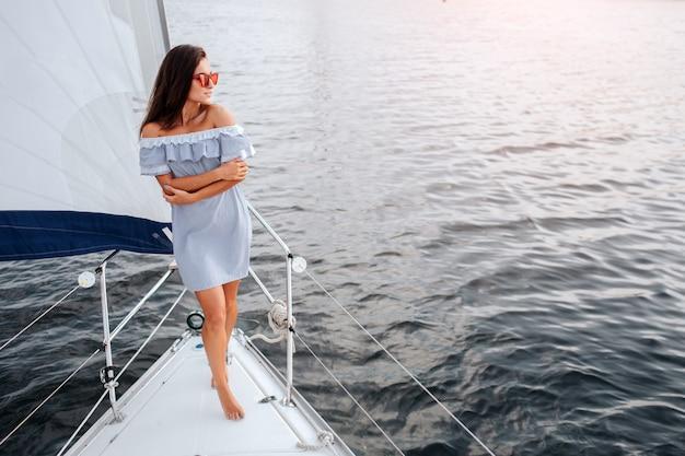 Model steht am yachtbogen und posiert.
