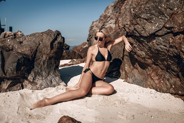 Model, trägt einen schwarzen bikini und eine sonnenbrille und posiert auf dem weißen sand des strandes neben riesigen felsen