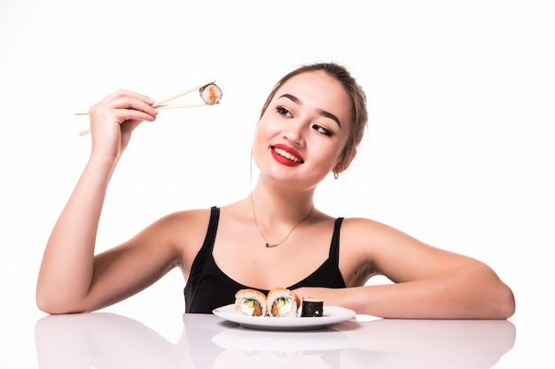 Modell asiatischer blick mit bescheidener frisur sitzen auf dem tisch essen sushi-rollen lächelnd isoliert auf weiß