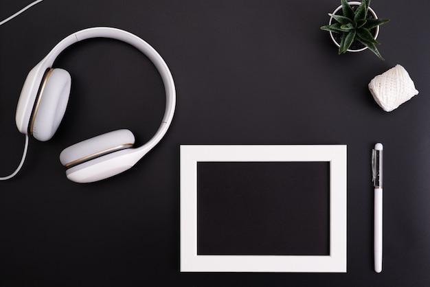 Modell, bilderrahmen, kopfhörer, stift und kaktus objekt auf schwarzem hintergrund schreiben