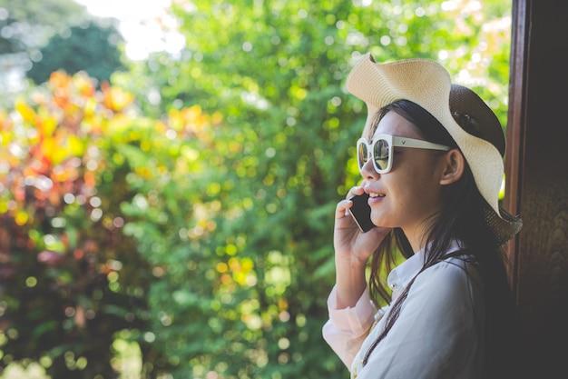 Modell, das am telefon auf einem natürlichen hintergrund spricht