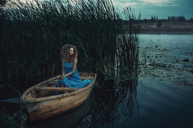 Modell, das blaues kleid trägt, posiert in einem boot auf dem wasser