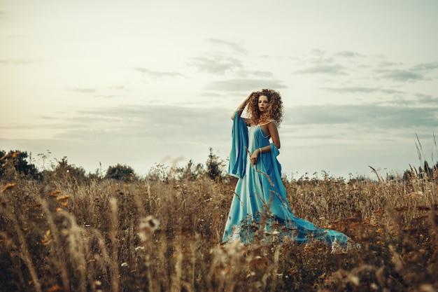 Modell, das blaues kleid trägt, posiert in einem wilden feld