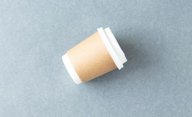 Modell, das eine kaffeepapiertasse lokalisiert auf hellgrauem hintergrund hält