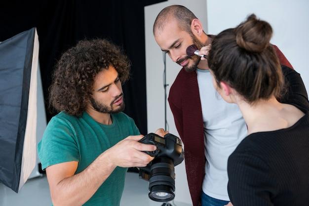 Modell, das fotos in der kamera betrachtet, während es sich für ein shooting vorbereitet
