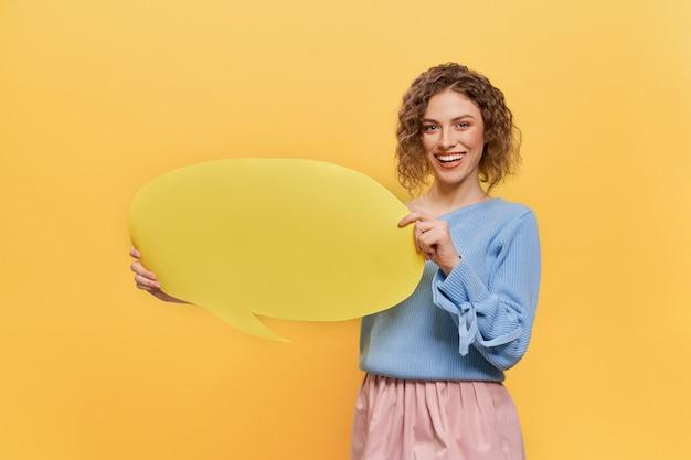 Modell, das gelbe leere spracheblase mit kopienraum hält.