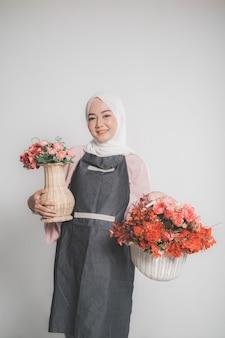 Modell, das hijab trägt und eine blume über beigem isoliertem hintergrund hält. stilvolle muslimische frau, die einen eimer der blume hält