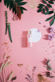Modell der flasche in den blumen auf rosa wand mit weißer kreisform. frühlingswand mit spa-zusammensetzung. flach liegen