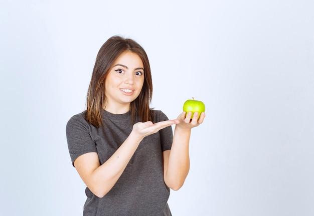 Modell der jungen frau, das an einem grünen apfel zeigt