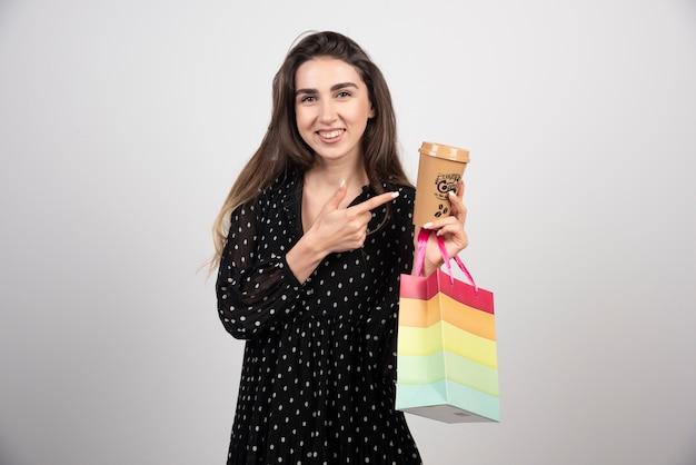 Modell der jungen frau, das auf eine kaffeetasse zeigt und eine geschäftstasche hält