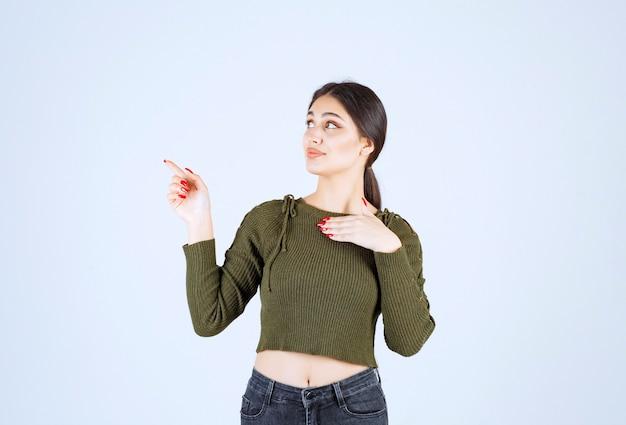 Modell der jungen frau, das mit dem zeigefinger zur seite steht und zeigt