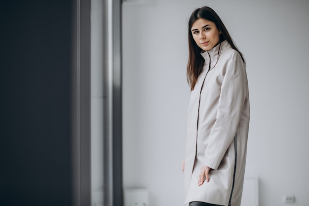 Modell der jungen frau, die langen grauen mantel trägt