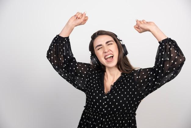 Modell der jungen frau, die musik in den kopfhörern tanzt und hört