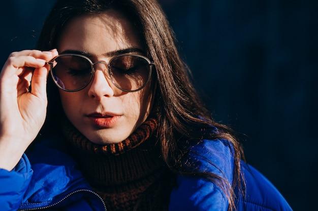 Modell der jungen frau in der blauen winterjacke auf einem blauen hintergrund