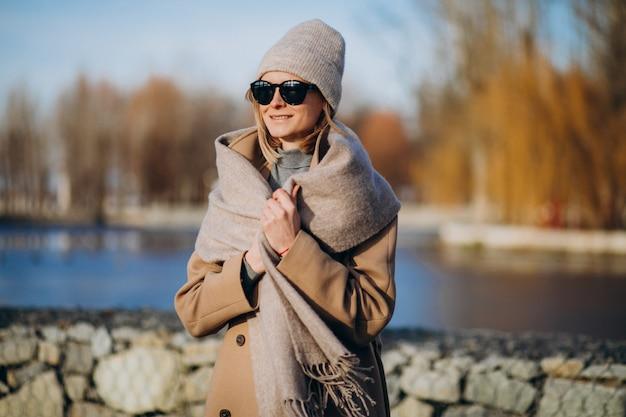 Modell der jungen frau kleidete im warmen mantel draußen im park an