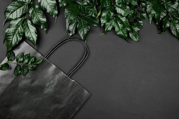 Modell der schwarzen einkaufstasche auf einem dunklen hintergrund mit grünen blättern, kreatives layout