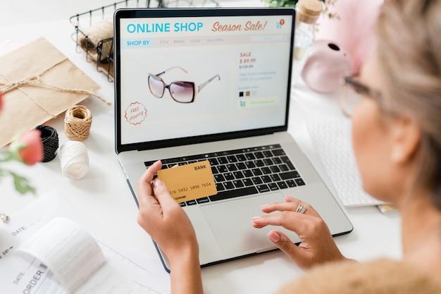 Modell der stilvollen brille auf laptop-display und hände der jungen käuferin über tastatur