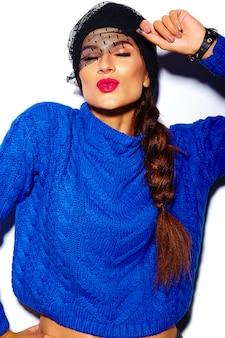 Modell der stilvollen schönen jungen frau des zaubers mit den roten lippen im blauen strickjackenhippie-stoff, der kuss gibt