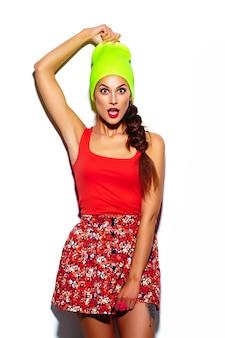 Modell der stilvollen schönen jungen frau des zaubers mit den roten lippen im hellen bunten hippie-stoff des sommers im gelben beanie