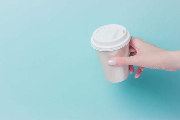 Modell der weiblichen hand eine kaffeepapierschale lokalisiert halten