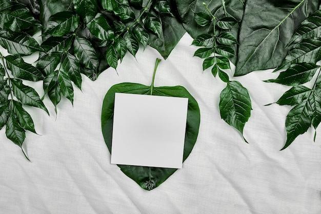 Modell der weißen leeren karte auf einem textilhintergrund mit grünen blättern an den seiten, flache lage, raum für text, draufsicht, produktbanner, naturkonzept.