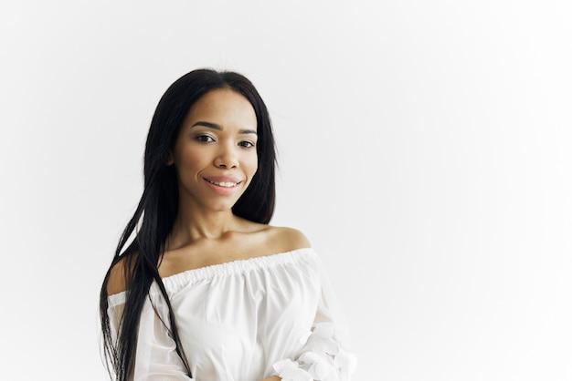 Modell des afrikanischen aussehens in der weißen kleiderkosmetik posiert